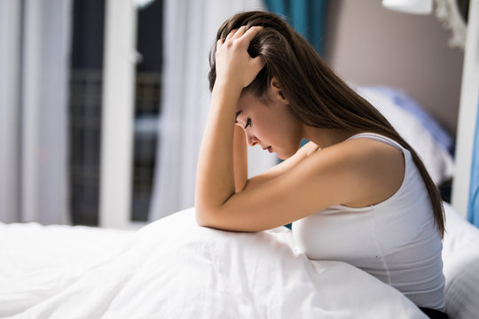 Woman with depression at night in her bed at home. Sad woman in bed at night
