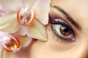 young pretty woman with flower orchid, makeup and eyeshadow