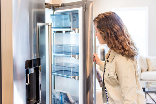 One young woman opening empty modern stainless steel chrome kitchen refrigerator, fridge looking inside, checking