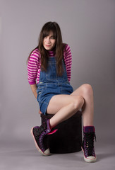 Cute Young Millennial Woman in Overalls Shoes Stripes on Stool