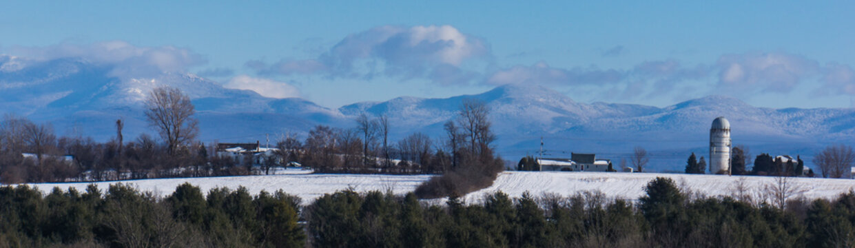 banner panorama view of the Green Mountains of Vermont USA in winter with snow, a farm with silo in foreground