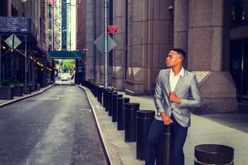 African American Businessman working, traveling in New York. A college student sitting on metal pillar on street, outside office building, thinking. Small car running on background. Filtered effect..