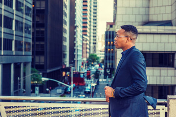 African American Businessman working in New York. Wearing blue jacket, glasses, a black man standing by railing on balcony, facing street, sad, thinking, lost in thought. Filtered effect..