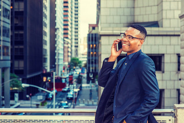 Happy African American Businessman working in New York. Wearing blue jacket, glasses, a young black man standing by railing on balcony, facing street with high buildings, smiling, talking on phone..