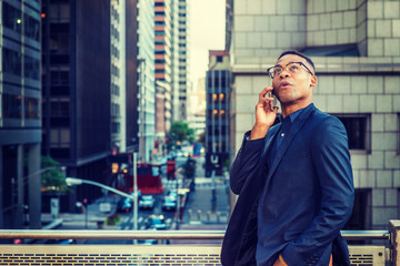 Happy African American Businessman working in New York, wearing blue jacket, glasses, standing by railing on balcony, facing street with high buildings, looking up, thinking, talking on cell phone..