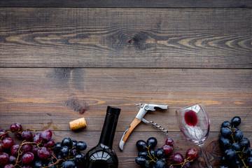 Open the wine. Corkscrew near bottle, glass, grape on wooden background top view copyspace