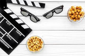 Popcorn, rusks for watching film. Clapperboard and glasses on white wooden background top view copyspace