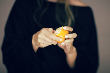 woman hands peeling orange tangerine, sensual studio shot with black background