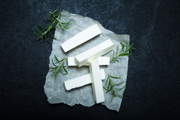 Fresh Feta Cheese with rosemary on black vintage background.