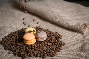 cake macarons on the coffee beans on the background of burlap linen