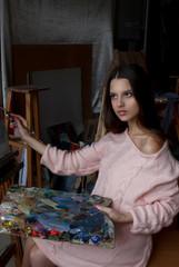 Young beautiful artist girl in the art studio