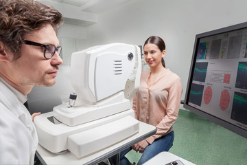 Eye care professional doing an OCT SLO retinal analysis Ophthalmologist in eyes clinic  examine Retinal Visual Function with a OCT SLO machine