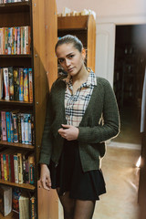 a сute slim young thin girl in а plaid shirt and a knitted green cardigan with a dark hair stands near a bookcase in the library