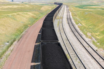Sunny afternoon and a long winding coal train from an open pit mine in the Powder River Basin of Wyoming.