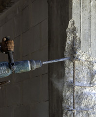 Construction worker with an electric demolisher hammer. Demolition of degraded concrete reinforced concrete pile for subsequent reconstruction of the structure
