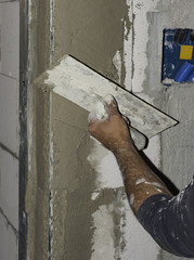 worker plastering tool plaster marble on interior plaster rough.  Selective focus