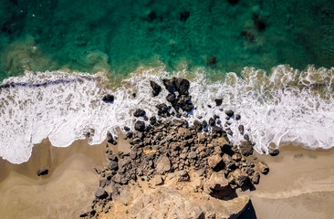 Drone view of waves hitting the rocks at the seashore