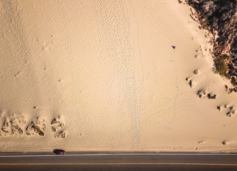 Drone view of a sand dune next to the highway with footprints and a parked car