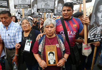 Radio Condor holds a picture of her son Amaro Condor as relatives of victims of the guerrilla conflict in the 80s and 90s march against President Pedro Pablo Kuczynski's pardon for former president Alberto Fujimori in Lima