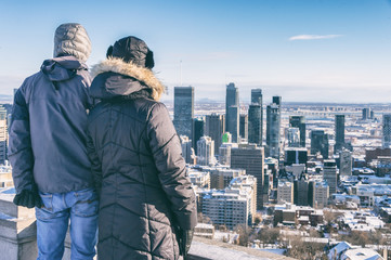 Couple looking at Montreal Skyline from Kondiaronk belvedere in winter.