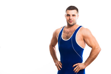 A young dark-haired man fighting Greco-Rican wrestling, a master of sports in grappling in a blue wrestling tights smiling and holding his hands at the waist against a white isolated background