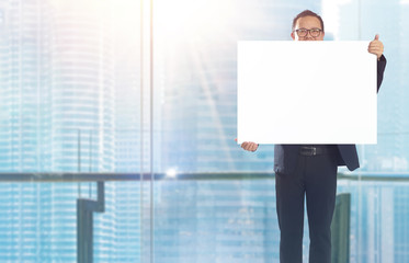 Businessman standing and holding white empty board in front of windows office overlooking the city at sunrise .