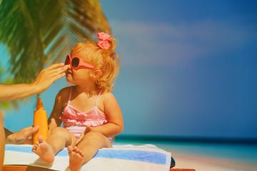 sun protection on beach - mother applying sunblock cream on daughter face