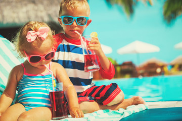 little boy and girl drinking juices on beach