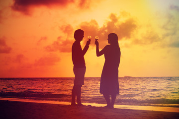 Silhouette of couple celebration drinking wine at sunset