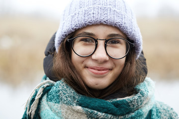 beautiful girl in round glasses and a knitted hat.