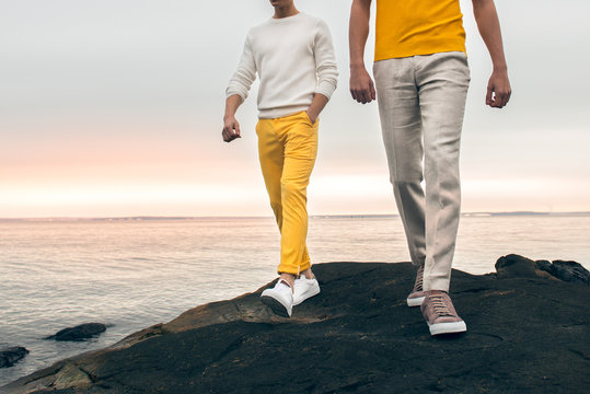 Two male models wearing fashionable spring summer outfit with colorful pants, t-shirt, sweater and shoes walking outdoors on the rock ocean beach