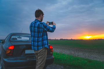 man taking picture of sunrise on highway while stop for resting
