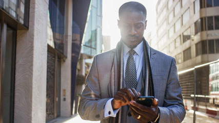 Handsome professional male walking in the city using his phone