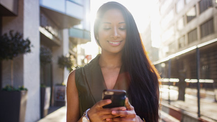 Attractive young woman smiling as she uses her phone walking down the street in the city