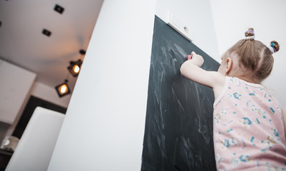 Little cute little girl paints with chalk on a blackboard at home, plays and wipes with a rag
