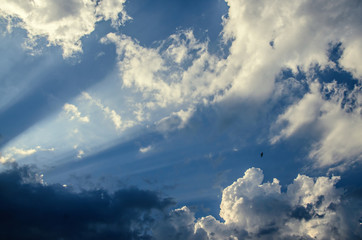 Dramatic cloudscape scene, colored sun lights on the blue sky, fluffy clouds