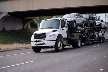 Mid size semi truck car hauler transporting vehicles on the road with bridge