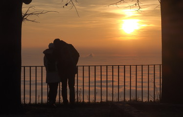 Couple admiring fog on the lowland at the sunset.