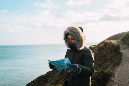Woman with map at seaside