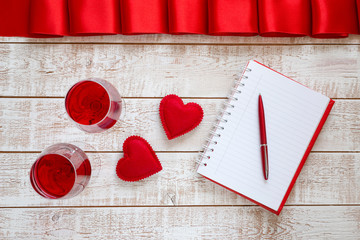 Valentines Day background with hearts and glasses of wine over white wooden table