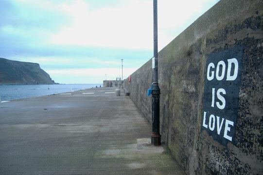 God is Love sign on Gardenstown Harbour, Scotland
