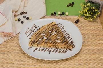 Folded crepe, Russian blini with chocolate sauce on white plate, chocolate chips on topping and dragees on the table