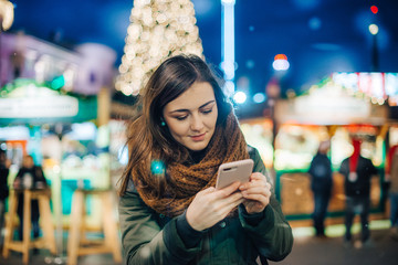 Beautiful young woman using her mobile phone in the street at night Fotomurales
