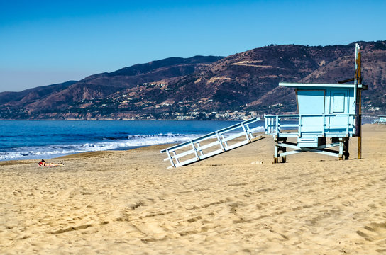 Scenic view of Malibu beach with lifeguard tower and a sunbathing woman
