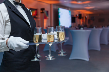 the waiter holds glasses with champagne on a tray