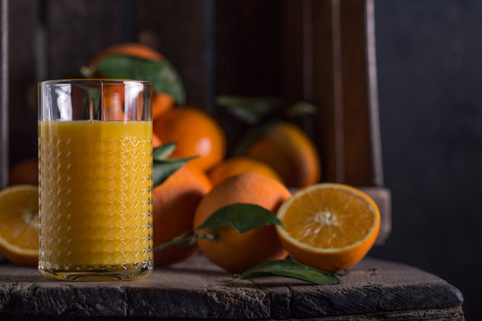 Close up of orange juice and oranges on wooden table