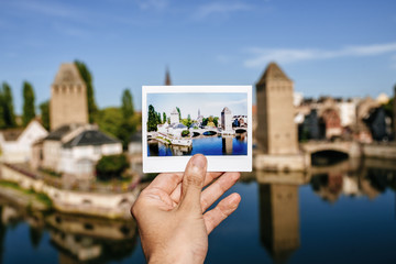 France, Strasbourg,hand holding instant photography of the Strasbourg towers with the same real landscape in the background