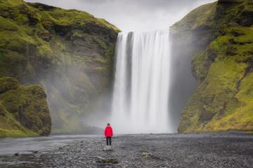 Woman standing near Skogafoss Waterfall in Iceland