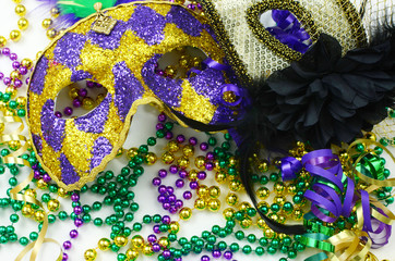 Mardi Gras image of close up detail of carnival masks, beads, ribbons and confetti in purple, green, gold and black on light background
