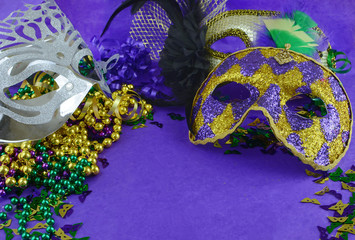 Mardi Gras border or frame of carnival masks, beads, ribbons and confetti in purple, green, gold and black on background of rough textured paper